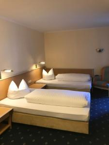 A bed or beds in a room at Hotel Ambiente Garni