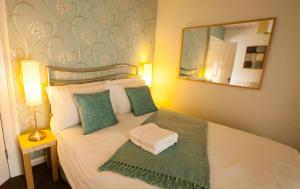 A bed or beds in a room at Hollybush Inn