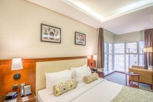 سرير أو أسرّة في غرفة في فندق جراند بلازا الضباب