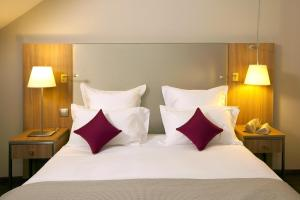 A bed or beds in a room at Residhome Roissy Park