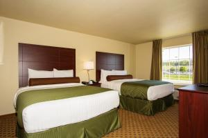 A bed or beds in a room at Cobblestone Inn & Suites - Corry