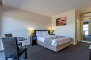 A bed or beds in a room at Sunshine Motor Inn