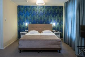 A bed or beds in a room at City Hotel Nieuw Minerva Leiden