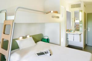 A bed or beds in a room at Ibis budget München Airport Erding