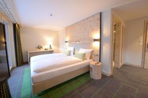 A bed or beds in a room at Alpenhotel Fleurs de Zermatt