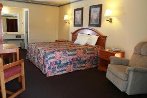 A bed or beds in a room at Claremore Motor Inn