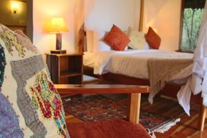 A bed or beds in a room at Ziwa Bush Lodge