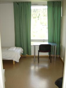 A bed or beds in a room at Kesähotelli Rentukka