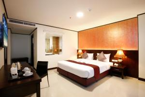 A bed or beds in a room at Orchid Resortel
