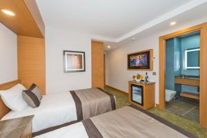 A bed or beds in a room at Bisetun Hotel