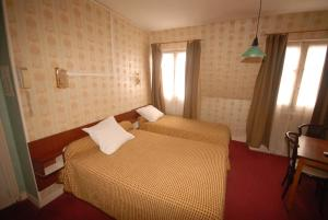 A bed or beds in a room at Hotel Gay Lussac