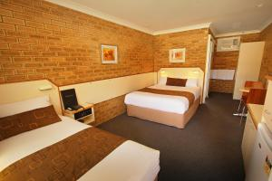 A bed or beds in a room at Garden City Motor Inn