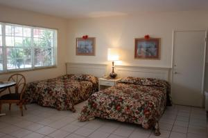 A bed or beds in a room at Beach and Town Motel