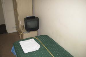 A television and/or entertainment centre at Chiswick Court Hotel - B&B