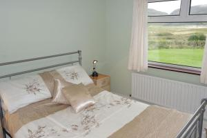 A bed or beds in a room at Ardara Cottage