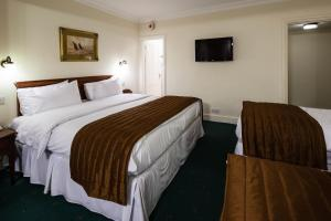 A bed or beds in a room at Best Western Swiss Cottage Hotel