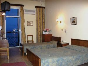 Ένα ή περισσότερα κρεβάτια σε δωμάτιο στο Παραδοσιακό Ξενοδοχείο Γύθειον