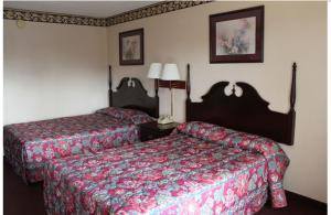 A bed or beds in a room at Studio 9 Inn & Suites