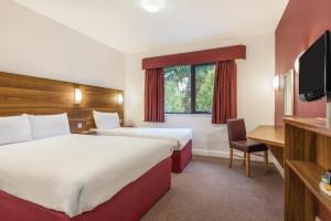 A bed or beds in a room at Days Inn Corley - Nec (M6)