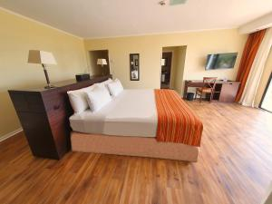 A bed or beds in a room at Xelena Hotel & Suites