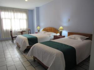 A bed or beds in a room at Las Orquídeas Hotel 3 estrellas