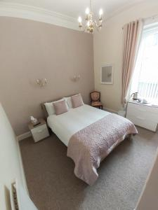 A bed or beds in a room at Elm House Hotel