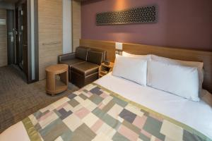 A bed or beds in a room at The Recenz Premium Gangnam Garosu-gil Hotel