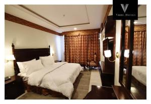 A bed or beds in a room at Viridi Hotels Islamabad