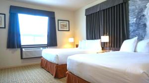 A bed or beds in a room at Super 8 by Wyndham Peace River AB