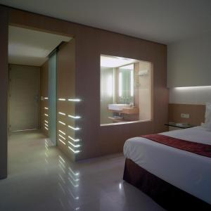 A bed or beds in a room at Lindos Blu Luxury Hotel-Adults only