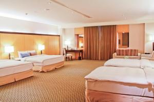 A bed or beds in a room at Queena Plaza Hotel