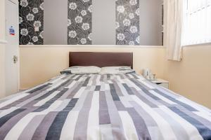 A bed or beds in a room at OYO The Longlands Hotel
