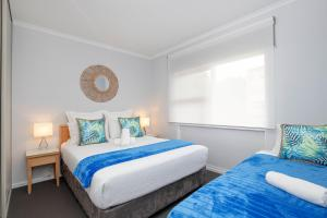 A bed or beds in a room at Glenelg Oasis Studios