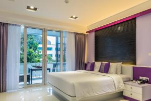 A bed or beds in a room at The L Resort Krabi