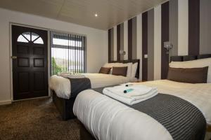A bed or beds in a room at Conwy Valley Hotel