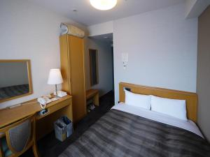 A bed or beds in a room at Hotel Route-Inn Sapporo Shiroishi