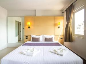 A bed or beds in a room at Montree Phuket Hotel