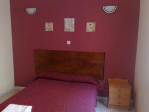 A bed or beds in a room at Pension El Cesar
