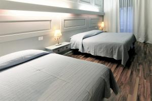 A bed or beds in a room at Hotel Les Arcades