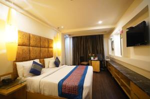 A bed or beds in a room at Airport Hotel Grand, New Delhi