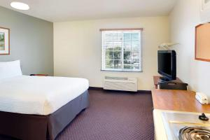 A bed or beds in a room at WoodSpring Suites Baton Rouge East I-12