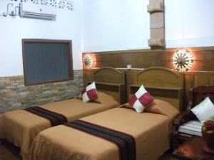 A bed or beds in a room at Mingalar Inn