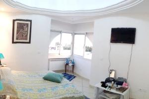 A television and/or entertainment center at Apartment with 2 bedrooms in Hammamet with wonderful sea view shared pool balcony 100 m from the beach