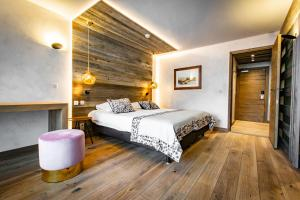 A bed or beds in a room at Hôtel Champs Fleuris Morzine