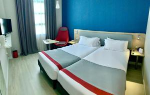 A bed or beds in a room at Holiday Inn Express Ciudad de las Ciencias, an IHG Hotel