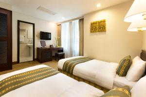 A bed or beds in a room at Shamrock Hotel