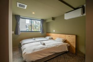 A bed or beds in a room at Wise Owl Hostels River Tokyo