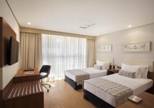 A bed or beds in a room at Windsor Plaza Brasília