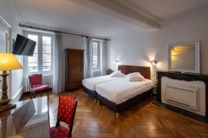Un ou plusieurs lits dans un hébergement de l'établissement Hôtel des Tonneliers