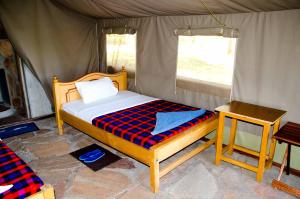 A bed or beds in a room at Semadep Mara Camp